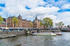 在中央驻地前面的运河船在阿姆斯特丹 库存图片