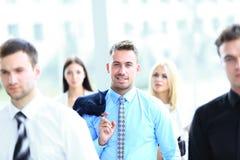 在中心站立他的队的Yung英俊的商人 免版税库存图片