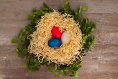 在中部在巢位于的木背景的复活节三色鸡蛋 免版税库存照片