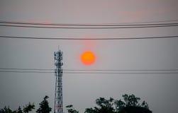 在中部的美好的充分的橙色日落在反对天空的电缆线之间 免版税库存照片
