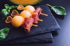 在串的五颜六色的点心用瓜和熏火腿 图库摄影
