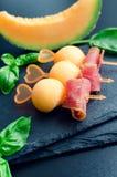 在串的五颜六色的点心用瓜和熏火腿 免版税库存图片