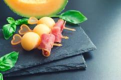 在串的五颜六色的点心用瓜和熏火腿 免版税库存照片