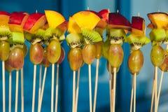 在串的果子素食点心用葡萄、猕猴桃和桃子在纯净的蓝色背景 承办酒席快餐服务 图库摄影