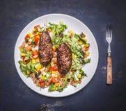在串的烤kebab用各种各样的菜沙拉在一块白色板材的有叉子木土气背景顶视图关闭的 库存照片