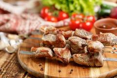 在串的猪肉烤肉串有新鲜蔬菜的 在开火烹调的开胃肉 库存照片