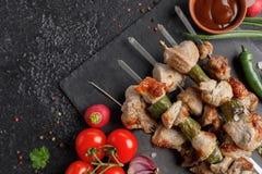 在串的诱人的烤肉串 在黑背景的静物画 与新鲜蔬菜和调味汁的开胃肉 免版税图库摄影