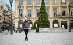 在为圣诞节装饰的一条巴黎人街道上的女孩 库存照片