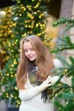 在为圣诞节装饰的一条巴黎人街道上的女孩 免版税库存照片