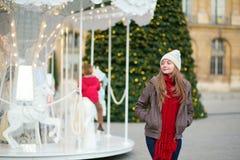 在为圣诞节装饰的一条巴黎人街道上的女孩 图库摄影