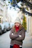 在为圣诞节装饰的一条巴黎人街道上的女孩 免版税图库摄影