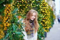 在为圣诞节装饰的一条巴黎人街道上的女孩 免版税库存图片