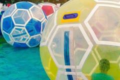 在主题乐园哄骗获得乐趣在水的巨型泡影球在游泳场 免版税库存图片