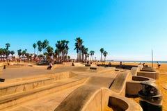在举世闻名的威尼斯海滩的Skatepark 有它的混凝土舷梯和棕榈树的冰鞋板公园是非常著名和普遍的 图库摄影