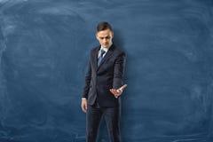 在举行一实施和看它的蓝色黑板背景的商人 免版税库存图片