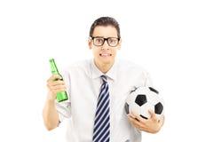 在举行啤酒瓶和橄榄球的衬衣的害怕的男性 库存照片