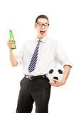 在举行啤酒瓶和橄榄球的衬衣的微笑的男性 库存图片