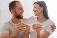 在举行妊娠试验的夫妇的选择聚焦 免版税库存图片