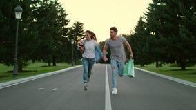 在举行手和赛跑在路的爱的愉快的夫妇在夏天公园 股票录像