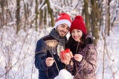 在举行礼物和bengals的红色帽子的夫妇户外 免版税库存照片