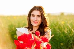 在举行鸦片花束和微笑的天空和日落的美丽的妇女 库存图片