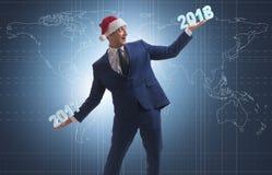 在举行2017年和2018年的圣诞老人帽子的商人 免版税图库摄影