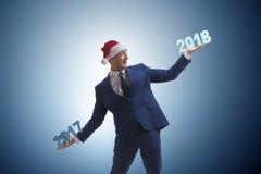 在举行2017年和2018年的圣诞老人帽子的商人 库存图片
