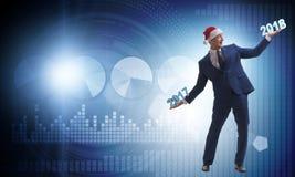 在举行2017年和2018年的圣诞老人帽子的商人 库存照片