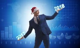 在举行2017年和2018年的圣诞老人帽子的商人 免版税库存图片