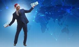 在举行2017年和2018年的圣诞老人帽子的商人 免版税库存照片