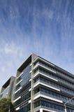在之下的现代玻璃大厦严重的天空 库存图片