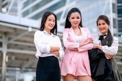 在之外的白天三个亚裔企业女孩作为确信与他们的工作并且微笑着表达愉快 库存照片