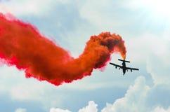 在之字形的飞机飞行与在天空的一股红色足迹烟 免版税库存图片