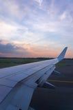 在之间离开,空中飞机的翼在云彩太阳海的  免版税库存照片