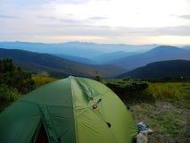 在乌克兰山的绿色旅游帐篷出于对树木丛生的小山考虑 免版税库存图片