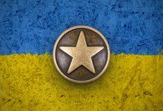 在乌克兰旗子背景的古铜色星 免版税图库摄影