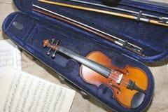在乐谱用纸背景的小提琴脖子 库存图片