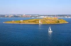 在乔治海岛全国古迹的灯塔,有风船的 库存图片