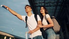 在乘坐出租汽车的爱的愉快的夫妇站立与行李在机场附近,旅行 休息,假期的概念 股票视频