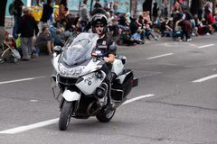 在乘坐在街道下的自行车的警察 库存照片
