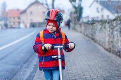 在乘坐对学校的滑行车的逗人喜爱的矮小的学龄前孩子男孩骑马 儿童活动室外在冬天,春天或 免版税库存照片