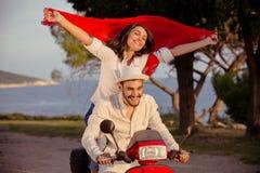 在乘坐摩托车、英俊的人和年轻性感的妇女的爱的夫妇移动 免版税图库摄影