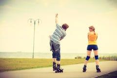 在乘坐的溜冰鞋的年轻夫妇户外 库存图片