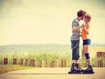 在乘坐的溜冰鞋的年轻夫妇户外 图库摄影
