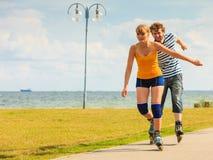 在乘坐的溜冰鞋的年轻夫妇户外 免版税库存图片