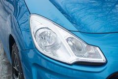 在乘客蓝色汽车的汽车车灯 免版税库存照片