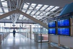 在乘客离开终端,关西国际机场,大阪里面的国际离开航行时刻表信息委员会 库存图片