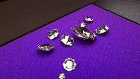 在九白色金刚石附近的照相机自转在一张紫色吸墨纸 皇族释放例证