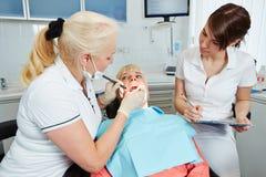 在习艺观看的牙医期间的牙科助理 库存照片