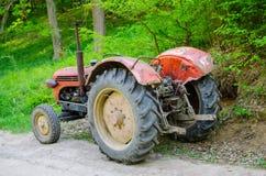 在乡下公路的老拖拉机 免版税图库摄影